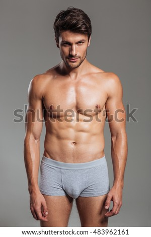 Portrait of a focused handsome muscular man in underwear standing isolated on a gray background