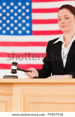 Portrait of a focused judge knocking a gavel with the camera focus on the gavel - stock photo