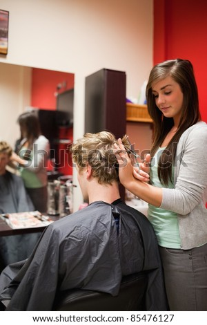 Portrait of a focused woman cutting a man's hair with scissors