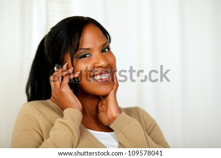 Portrait of a fresh woman looking to you and talking on mobile at home indoor - stock photo