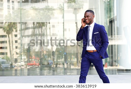 Portrait of a friendly african businessman walking in the city talking on mobile phone  - stock photo