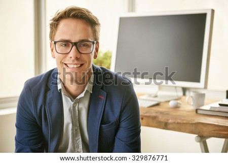 Portrait of a friendly and fashionable young professional man smiling at the camera while sitting in his office - stock photo