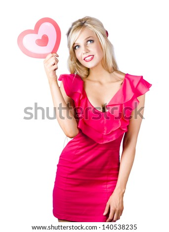 Portrait of a friendly beautiful blonde woman in a red dress holding red love heart symbol. Looking for love concept - stock photo
