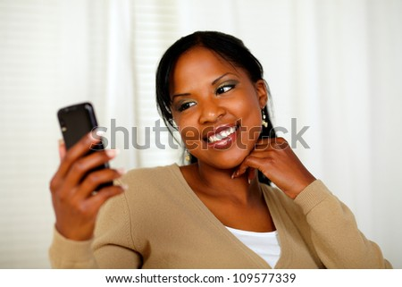 Portrait of a friendly black woman sending a text message by the cellphone - stock photo