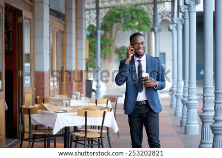 Portrait of a friendly businessman walking and talking on mobile phone - stock photo