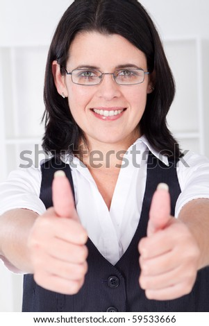 Portrait of a friendly businesswoman giving thumbs up - stock photo