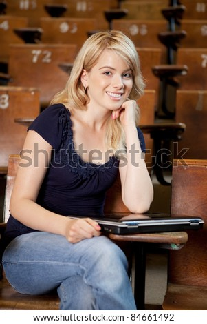 Portrait of a friendly college girl in a lecture hall with laptop computer