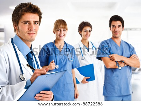 Portrait of a friendly doctor in front of his team - stock photo