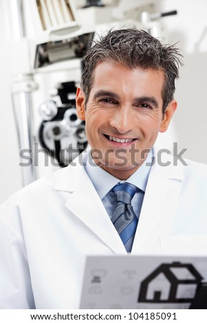 Portrait of a friendly eye doctor smiling at his clinic - stock photo