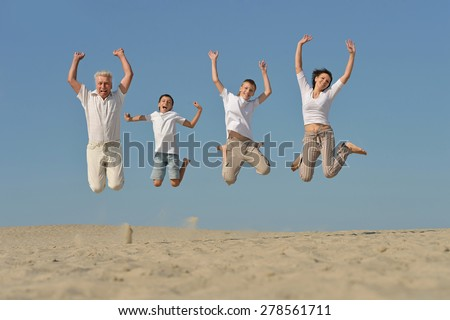 Portrait of a friendly family on blue sky background - stock photo