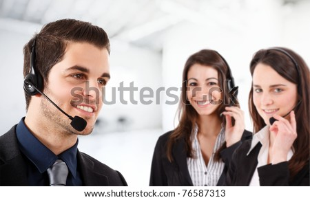 Portrait of a friendly phone operator. Two female operators in the bright and blurred background. - stock photo