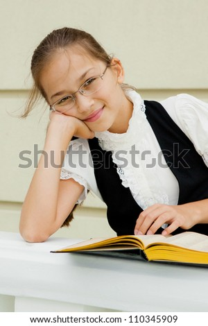 Portrait of a friendly school girl student in school uniform and holding book - stock photo