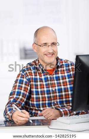 Portrait of a friendly smiling mature balding caucasian man, wearing glasses, sitting at a desk and using a digital pen tablet while looking at the computer screen in his office - stock photo