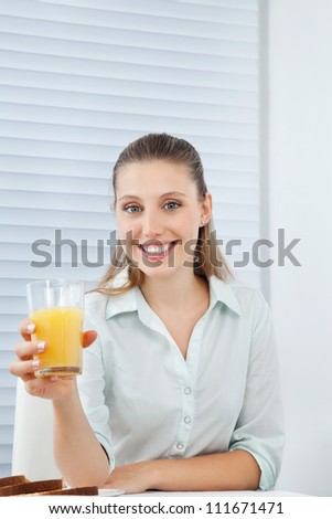 Portrait of a friendly young businesswoman holding glass of orange juice