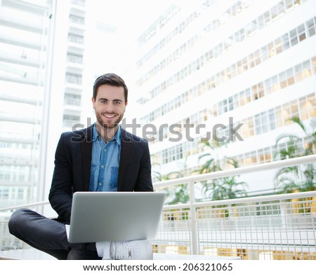 Portrait of a friendly young man using laptop inside building - stock photo