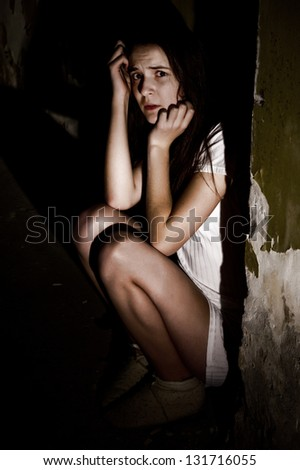 Portrait of a frightened teenage girl in a dark cellar
