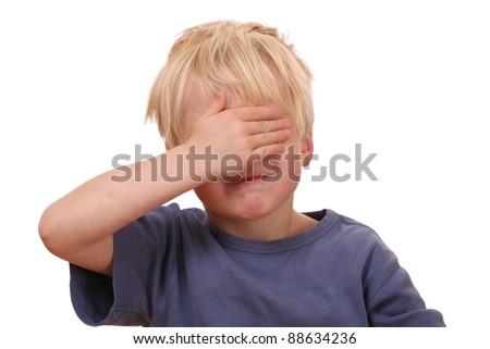 Portrait of a frightened young boy covering his eyes - stock photo