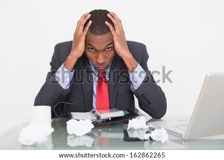 Portrait of a frustrated young Afro businessman with head in hands at  desk against white background