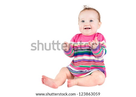 Portrait of a funny baby girl in a pink striped dress, isolated on white