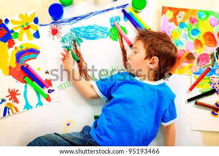 Portrait of a funny boy enjoying his painting. Education. - stock photo