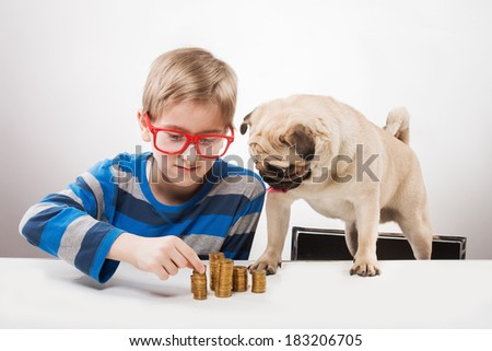 Portrait of a funny boy in red-framed glasses looking at piles of coins
