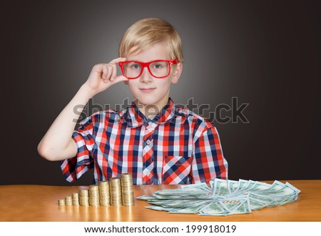 Portrait of a funny boy in red-framed glasses with cash banknotes and coins - stock photo