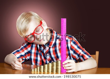 Portrait of a funny boy in red-framed glasses with the piles of coins and a ruler - stock photo