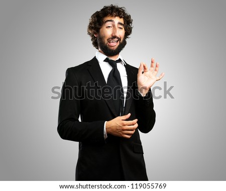 Portrait Of A Funny Businessman against a grey background - stock photo