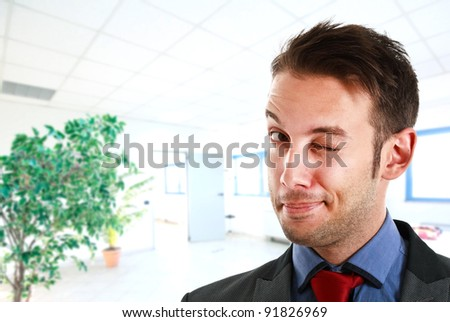Portrait of a funny businessman winking at you - stock photo