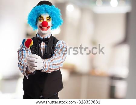 portrait of a funny clown holding a lollipop - stock photo