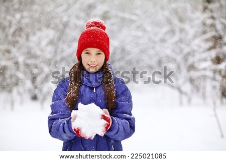 portrait of a funny girl on a walk in the winter. teen outdoors - stock photo