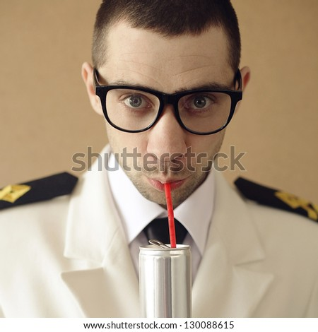 Portrait of a funny handsome hipster groom (dude) in trendy glasses drinking something from tin can through red plastic sipper. daylight. studio shot - stock photo