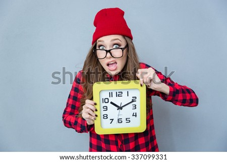 Portrait of a funny hipster woman holding wall clock over gray background - stock photo