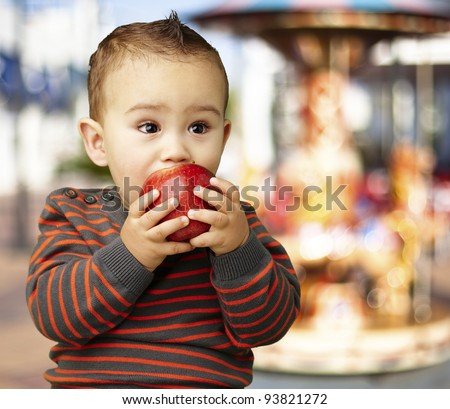 portrait of a funny kid eating a red apple against a carousel background - stock photo