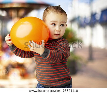 portrait of a funny kid holding a big orange balloon against a carousel - stock photo