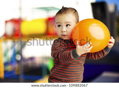 portrait of a funny kid holding a big orange balloon against an abstract background