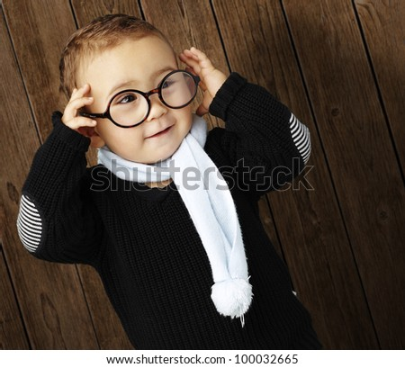 portrait of a funny kid holding his glasses  against a wooden wall - stock photo