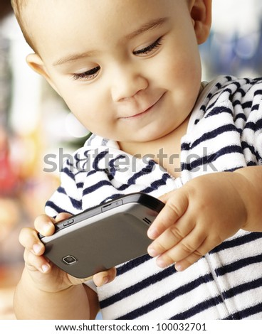 portrait of a funny kid playing with a mobile against an abstract background - stock photo