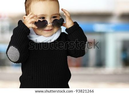 portrait of a funny kid wearing heart sunglasses against a street background - stock photo