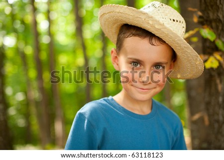Portrait of a funny kid with straw hat outdoor - stock photo