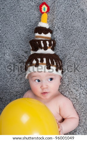 Portrait of a funny kid with the cap in the form of a cake on his head. - stock photo