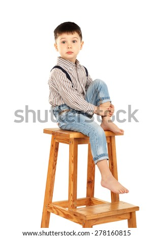 Portrait of a funny little boy sitting barefoot on a high stool isolated on white background