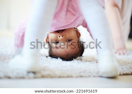 Portrait of a funny little girl summersaulting - stock photo