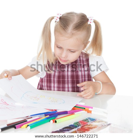 Portrait of a funny little schoolgirl drawing on the table over white