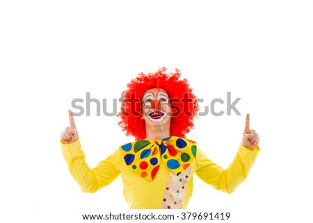 Portrait of a funny playful clown in red wig pointing and looking upwards, isolated on a white background - stock photo