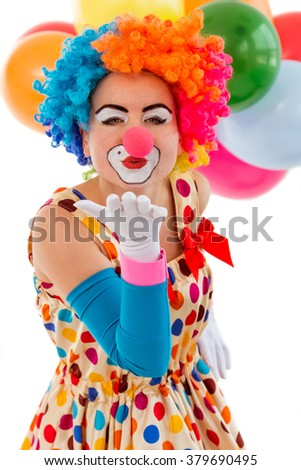 Portrait of a funny playful female clown in colorful wig air kissing and looking at camera, in the background balloons, isolated on a white - stock photo