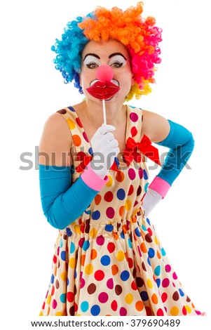 Portrait of a funny playful female clown in colorful wig covering mouth with lips lollipops and looking at camera, isolated on a white background - stock photo