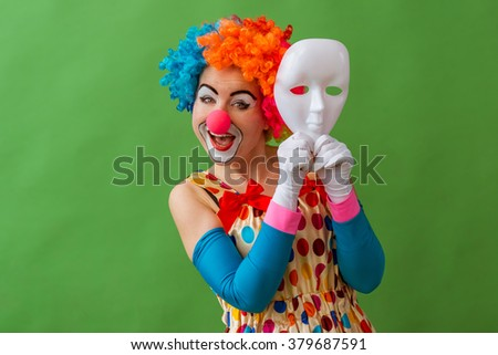 Portrait of a funny playful female clown in colorful wig holding a mask near her face and smiling, standing on a green background - stock photo