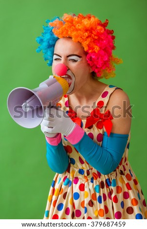 Portrait of a funny playful female clown in colorful wig screaming into loudspeaker, standing on a green background - stock photo