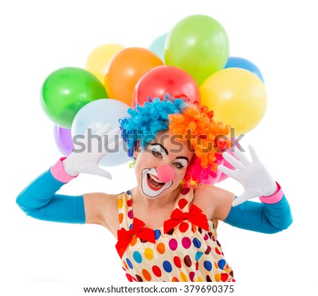 Portrait of a funny playful female clown in colorful wig teasing, looking at camera and showing palms, in the background balloons, isolated on a white - stock photo